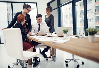 Buy stock photo Shot of a group of businesspeople using a laptop together during a meeting in an office