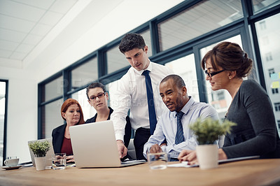 Buy stock photo Cropped shot of group of businesspeople using a laptop together during a meeting in an office
