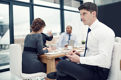 Buy stock photo Cropped shot of a businessman using a digital tablet during a meeting with his colleagues