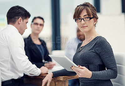 Buy stock photo Portrait of a businesswoman using a digital tablet during a meeting with her colleagues