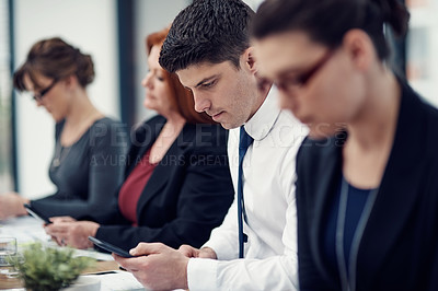Buy stock photo Cropped shot of a group of businesspeople texting on their cellphones in an office
