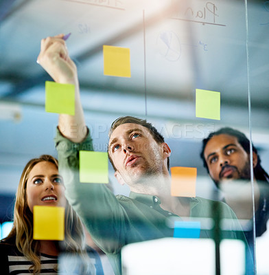 Buy stock photo Shot of colleagues having a brainstorming session with sticky notes at work