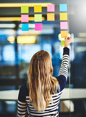 Buy stock photo Rearview shot of a woman having a brainstorming session with sticky notes at work