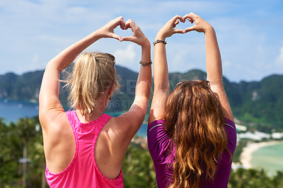 Buy stock photo Rear view shot of two young woman making a heart gesture while facing a scenic landscape