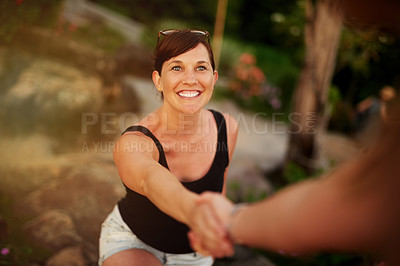 Buy stock photo Shot of a young woman being led by the hand while exploring outside