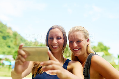Buy stock photo Cropped shot of two young girlfriends taking selfies on the beach