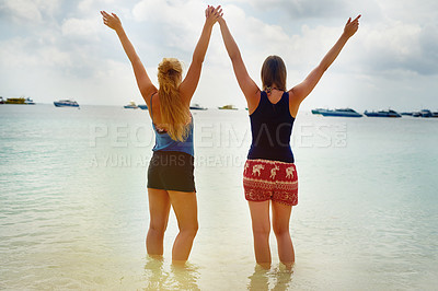 Buy stock photo Rearview shot of two young girlfriends enjoying a day at the beach on a summer's day