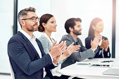 Buy stock photo Shot of a group of businesspeople applauding while sitting in the boardroom