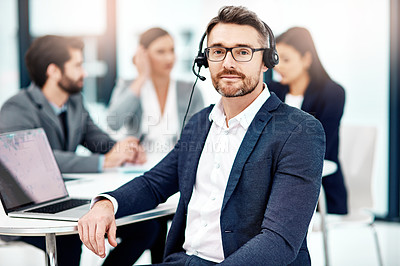 Buy stock photo Portrait of a male telephone operator in the office with his colleagues in the background