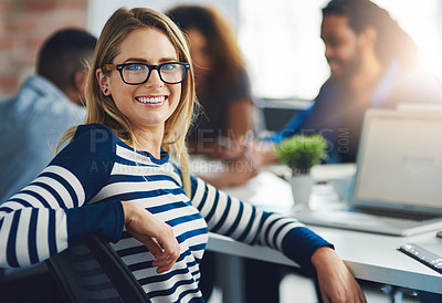 Buy stock photo Portrait of a young designer sitting in an office with her colleagues in the background