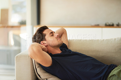 Buy stock photo Cropped shot of a handsome young man resting on his sofa at home