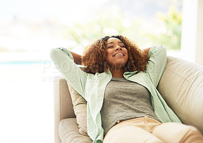 Buy stock photo Cropped shot of an attractive young woman resting on her sofa at home