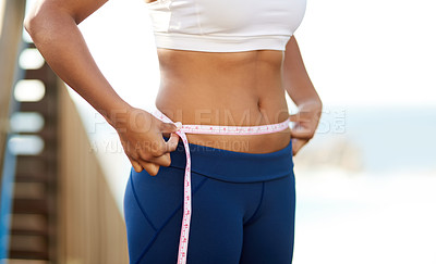Buy stock photo Cropped shot of an unrecognizable young woman measuring her waistline