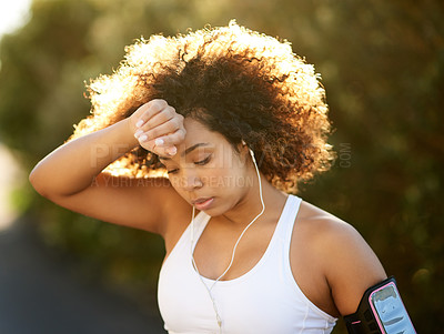 Buy stock photo Shot of an attractive young woman wiping her brow during her workout