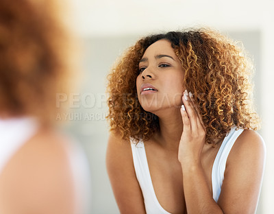Buy stock photo Shot of a young woman inspecting her skin in front of the bathroom mirror