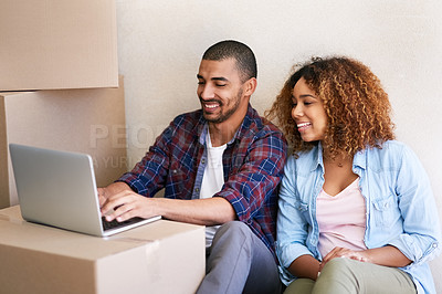 Buy stock photo Shot of a young couple using a laptop while sitting among boxes on moving day