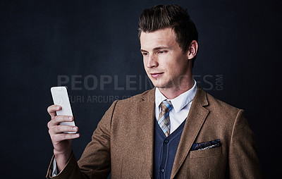Buy stock photo Studio shot of a young businessman using his cellphone against a dark background