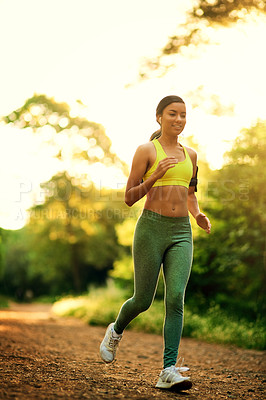 Buy stock photo Shot of a young woman running in a natural environment