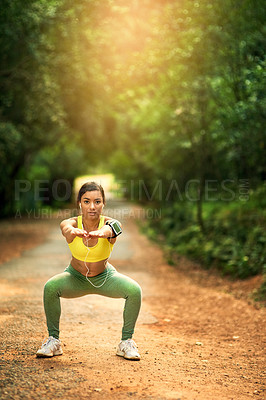 Buy stock photo Shot of a sporty young woman dong squats in a natural environment
