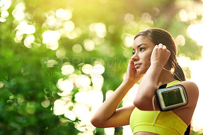 Buy stock photo Shot of a young woman putting in her earphones before her run