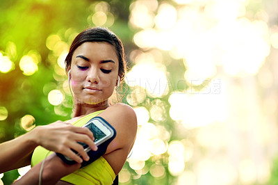 Buy stock photo Shot of a young woman selecting a playlist before her run