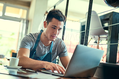 Buy stock photo Cropped shot of a young man working on a laptop in his coffee shop
