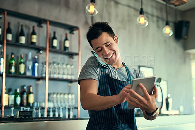 Buy stock photo Shot of a young man taking orders via cellphone and logging them on his tablet