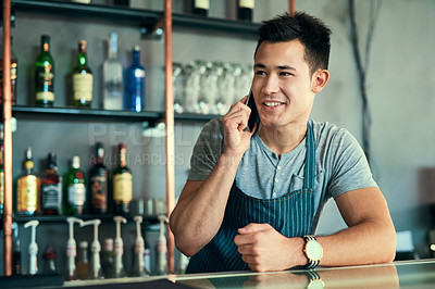 Buy stock photo Cropped shot of a young man taking orders via cellphone in his coffee shop