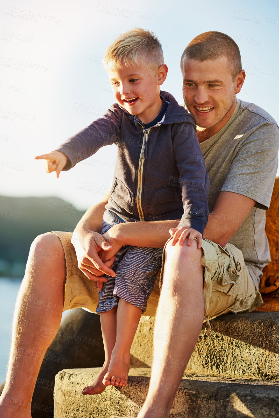 Buy stock photo Shot of a father bonding with his little boy while they sit by the harbor