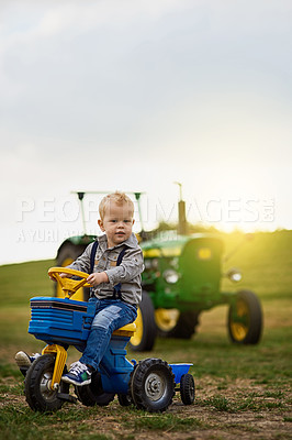 Buy stock photo Portrait of an adorable little boy riding a toy truck on a farm