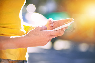 Buy stock photo Cropped shot of an unrecognizable young woman using a smartphone outside