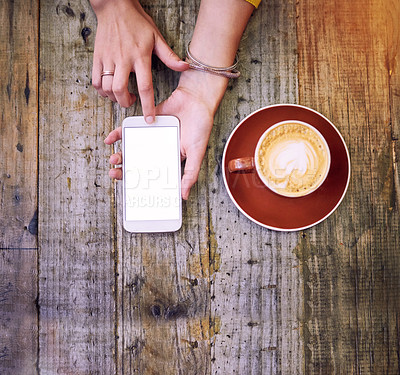 Buy stock photo High angle shot of a woman using her cellphone and having a cup of coffee