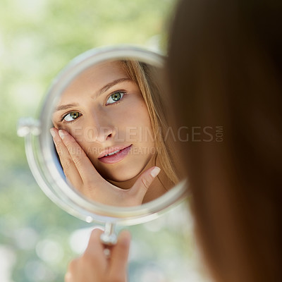 Buy stock photo Shot of an attractive young woman touching her skin in front of the mirror