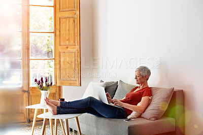Buy stock photo Shot of a mature woman relaxing on her sofa at home using a laptop