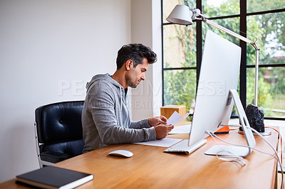 Buy stock photo Shot of a young man sorting paperwork while sitting at a desk in his home office