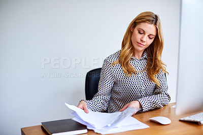 Buy stock photo Shot of a young woman sorting paperwork while sitting at a desk in her home office