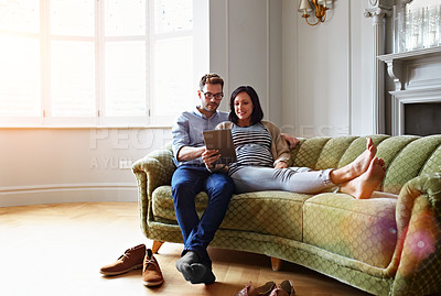 Buy stock photo Shot of a pregnant woman and her husband sitting on their sofa using a digital tablet