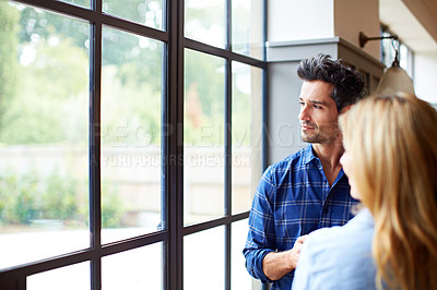 Buy stock photo Shot of a young couple looking out of a window together at home