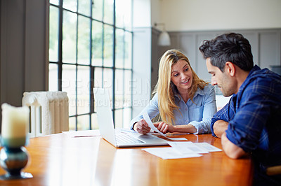 Buy stock photo Shot of a young couple sitting together at their kitchen table paying bills online