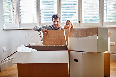 Buy stock photo Portrait of a smiling couple sitting in a large box while moving into a new home
