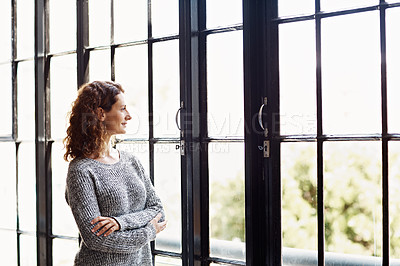 Buy stock photo Shot of a mature woman standing in her home looking through a window