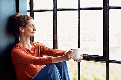 Buy stock photo Shot of an attractive mature woman sitting on a window sill at home drinking a cup of coffee