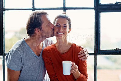 Buy stock photo Shot of a man kissing his wife on the cheek while drinking coffee together in the morning