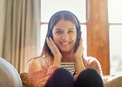 Buy stock photo Portrait of a smiling young woman sitting on her sofa listening to music on headphones