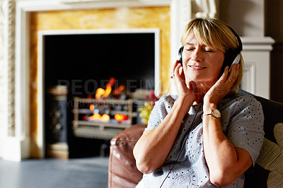 Buy stock photo Shot of a mature woman sitting back on her sofa listening to music on headphones