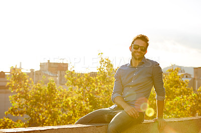 Buy stock photo Portrait of a smiling young man sitting on a rooftop at sunset with the city in the background