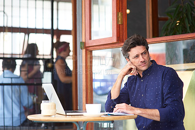Buy stock photo Shot of a man using a laptop while sitting at a sidewalk cafe
