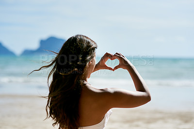 Buy stock photo Shot of a young woman shaping a heart while looking at the scenery at the beach