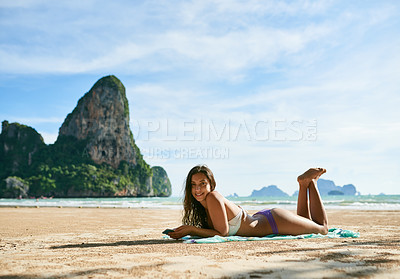 Buy stock photo Shot of a beautiful young woman relaxing on the beach while using her phone