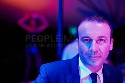 Buy stock photo Portrait of a seedy businessman in a go go bar with a woman dancing on a pole behind him